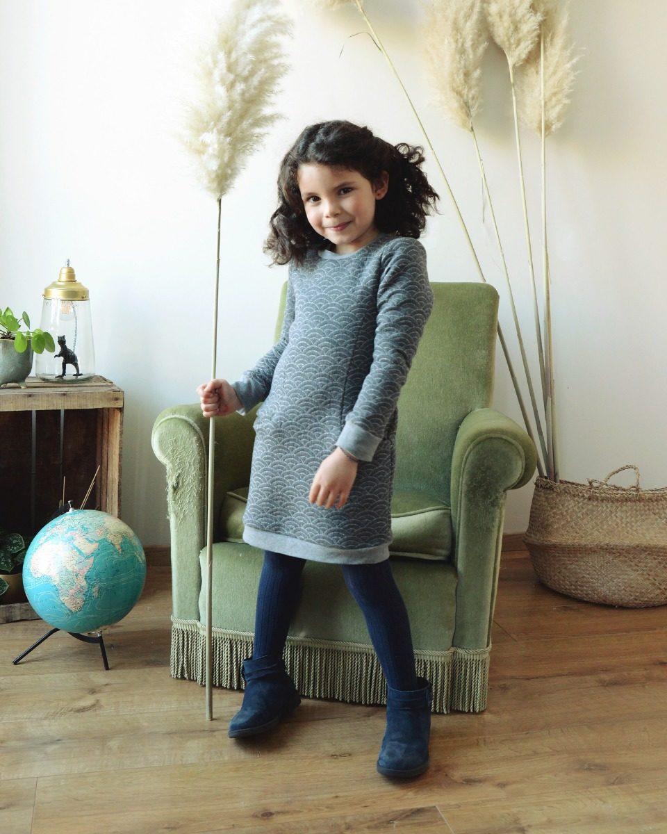 une image du patron de couture fille sur mesure de la robe manches longues simple et droitre pour hiver. Ce patron est très facile à coudre pour les débutants. Cette robe sweat de petite fille avec poches est en tissu jersey matelassé bleu.